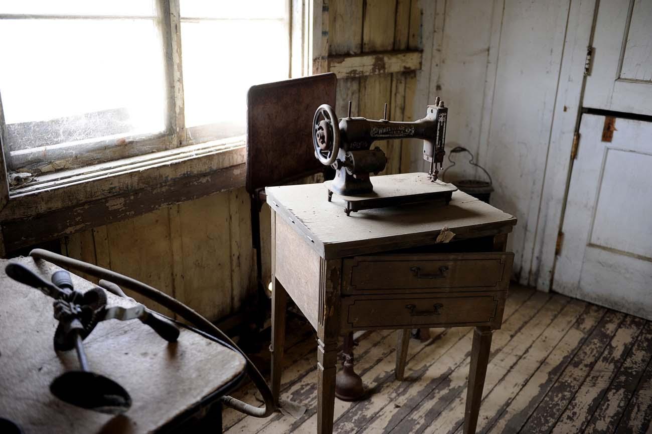 En gammal dammig symaskin står kvar vid ett fönster